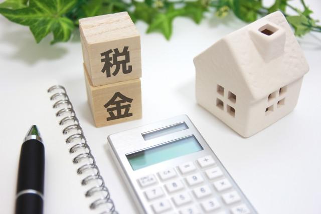 家と税金の積み木と電卓とペンとノート