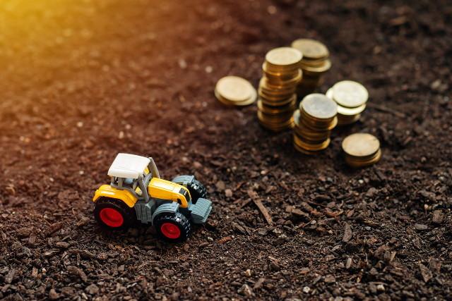 土の上に置かれたおもちゃのトラクターとコイン