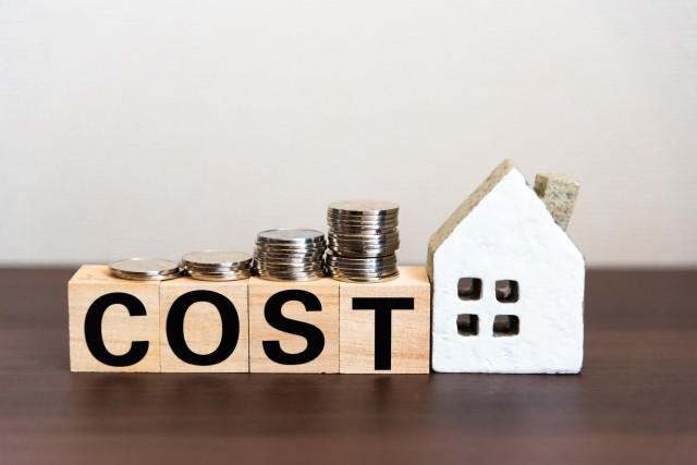 COSTと書かれた積み木とコインとおもちゃの家